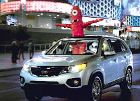 Scene from Kia commercial: characters appeared at auto show, on display in Times Square