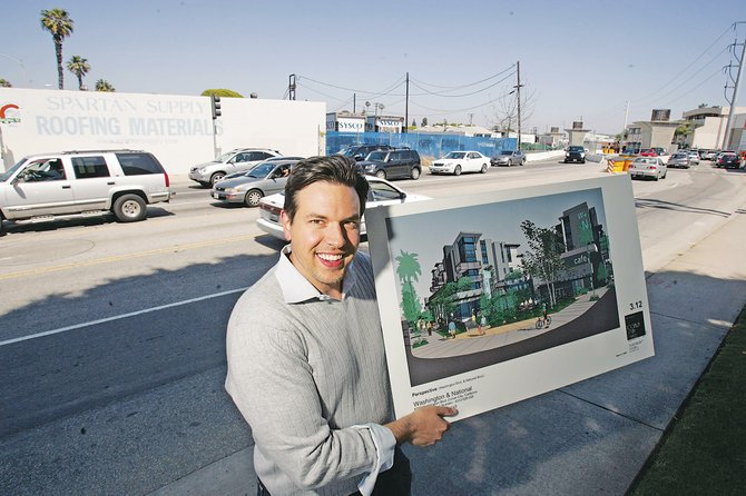 Legado's Derek Jones with a rendering of a mixed-use project located near a future Expo station in Culver City.