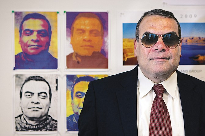 Ahmed Enany in front of several self-portraits at his office in downtown Los Angeles.