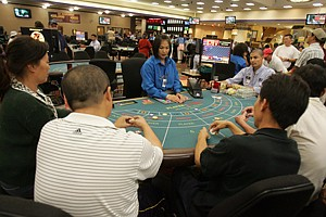 Dealer and players at a Commerce Casino EZ Baccarat table.