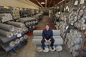 Peter Kim, CEO of denim maker Hudson Jeans, with reams of material at the company's Commerce warehouse.