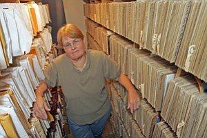 Stephanie Rinaldo, owner of Hollywood Sheet Music, with rows of scores at her home in Valley Glen.