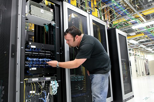Network technician Aaron Kindlesparker works in the switch room floor, which features equipment that processes voice and data calls, at a Verizon Wireless facility in North County.