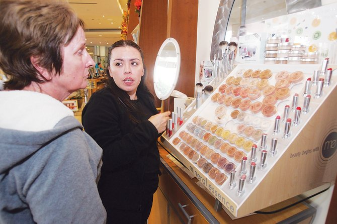 Customer, left, is helped with a selection of Murad skin care products.