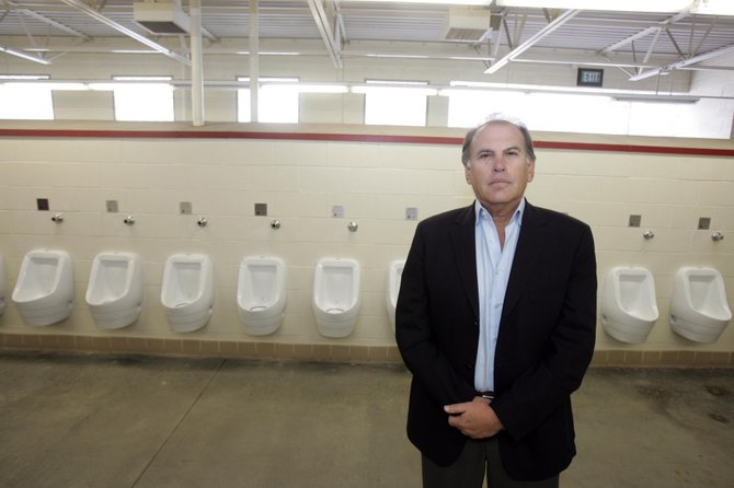 Falcon CEO James Krug in a Los Angeles Coliseum men's room with the company's waterless urinals.