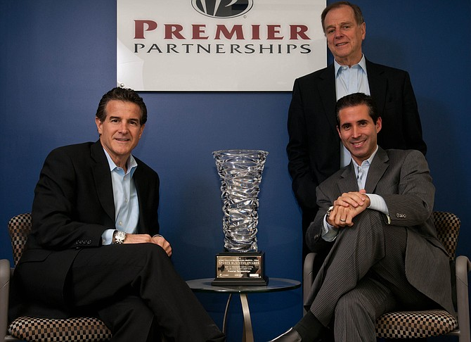 From left, Premier Partnerships' Randy Bernstein, Alan Rothenberg, standing, and Jeff Marks with Sports Business Journal award at Santa Monica office.