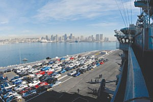 With sailors' vehicles on the flight deck, aircraft carrier USS Nimitz prepares to leave San Diego for its new home port in Washington state.