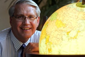 Chief Executive and frequent traveler Dean Scarborough with a globe in his Pasadena office.