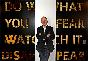 David Angelo, chairman and chief creative officer, in front of a saying, 'Do what you fear, watch it disappear,' at the ad agency's headquarters in El Segundo.