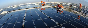 Edison workers install solar panels on a rooftop.