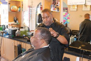 Mario Lewis, the owner of Imperial Barber Shop, cuts the hair of a customer. Lewis credits the loans he received from Accion San Diego for his ability to expand his business.