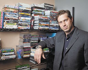 Discs: Ryan Kugler with some of the CDs and DVDs distributed by his Burbank company, DVA Inc. The fading popularity of the formats is big business for Kugler.