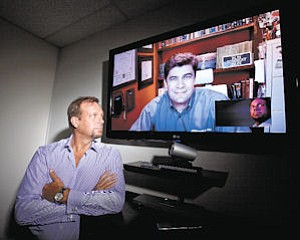 Telemedicine: Specialists On Call CEO Joe Peterson (left) uses technology to connect with Dr. Leonard Dimitri DaSilva (right), a neurologist working in Tallahassee, Fla.