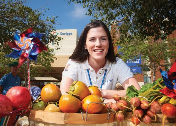 Tracey Lavery, a benefits manager at Scripps Health, shows some of the healthy offerings available at Scripps farm stand, part of the 'voluntary benefits' offered by the nonprofit, which include discounted cellular service and theme park tickets.