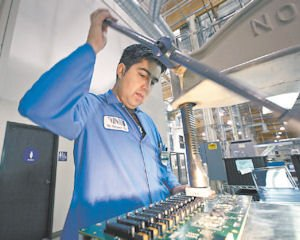 Press: A worker applying parts to a circuit board.