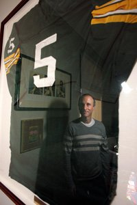 Funny or Die CEO Dick Glover, at his Hollywood office, reflected in glass cover over Paul Hornung's jersey.