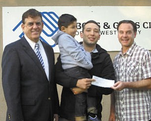 Support: Eric Castillo (center) with son, Jaylen, at the check presentation.