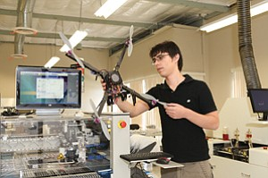 Jordi Munoz Bardales, CEO and co-founder of 3D Robotics Inc., stands back as a miniature, six-rotor drone hovers. Flanking Munoz are two machines used to produce autopilot circuit boards.