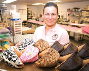 Icing: Chief Confectionary Officer, Daria Artem, holds a pan with giant fortune cookies at Lady Fortunes bakery.