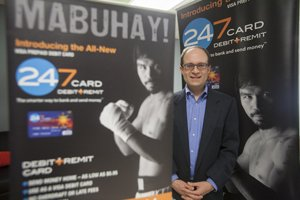 Banking & Finance Quarterly: Lance Rosenzweig at 24/7 Card in Brentwood, with promotional posters featuring boxer Manny Pacquiao.