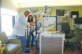 Dr. Matt Sebald, director of the NICU at Kaiser, assists new mom Lauren Mancuso and her baby. Kaiser recently completed a $20M makeover of its NICU facilities.