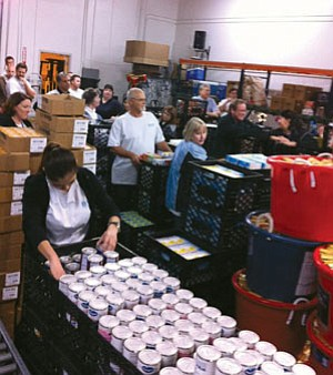 Employees from BluFi Lending packed nearly 20,000 meals into boxes to aid San Diego seniors living in poverty.