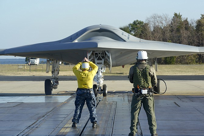 "On a simulated aircraft carrier flight deck in Maryland, a yellow-shirted U.S. Navy aviation boatswain's mate directs an X-47B unmanned aircraft. Since there is no pilot in the aircraft, a deck operator watches the ""yellow shirt"" and relays his commands to the aircraft using an elaborate, arm-mounted console."