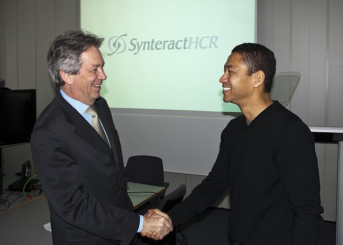 Dr. Francisco Harrison, left, founder of Harrison Clinical Research, shakes hands with Wendel Barr, CEO of SynteractHCR. Synteract's acquisition of Munich, Germany-based Harrison Clinical Research Group GmbH gives it a much bigger global presence.