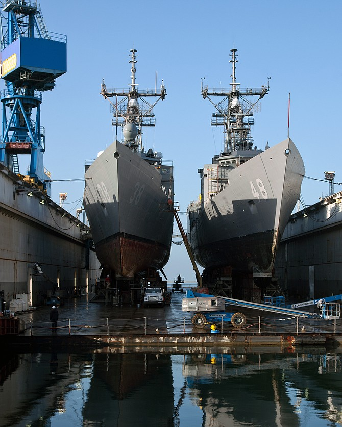 The frigates USS Curts and USS Vandegrift sit in dry dock at General Dynamics Nassco in 2011, left. The Nassco shipyard accommodates new ship construction as well as U.S. Navy ship repair. The view at right is at sunrise. Nassco recently announced that 290 subcontractors and 375 workers who had been facing possible layoffs will continue to work.