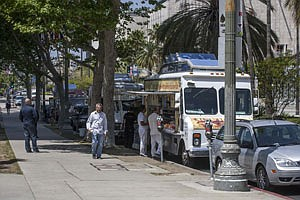 Customers check out food trucks parked along Miracle Mile.