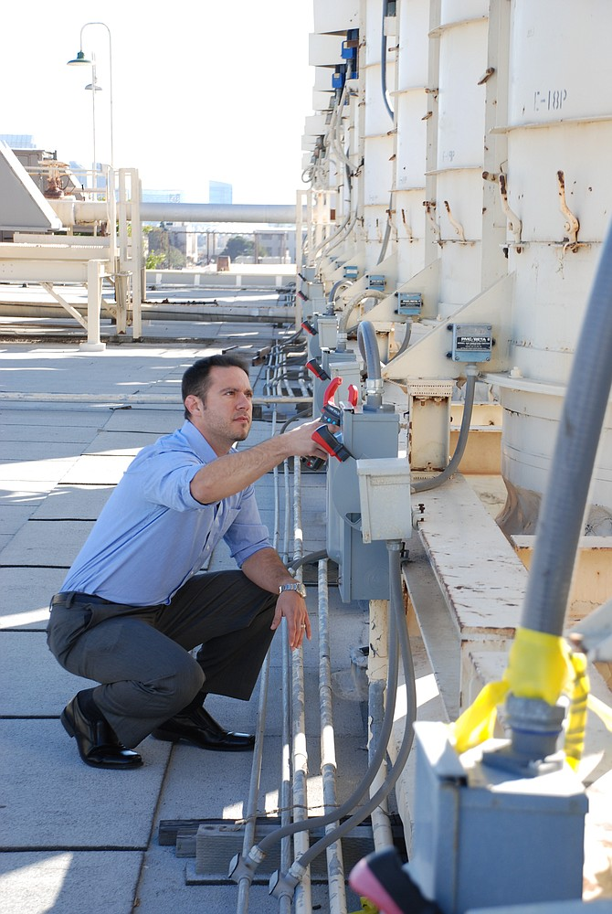 Fleet Readiness Center Southwest command energy and water conservation manager Matthew Schreck prepares to monitor the electrical output of one of the industrial exhaust fans belonging to the paint facility.