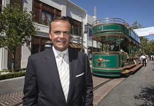 Rick Caruso with fixed-rail trolley at Grove retail center.
