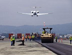 A jet passes over the crew repairing the main runway at Van Nuys Airport.