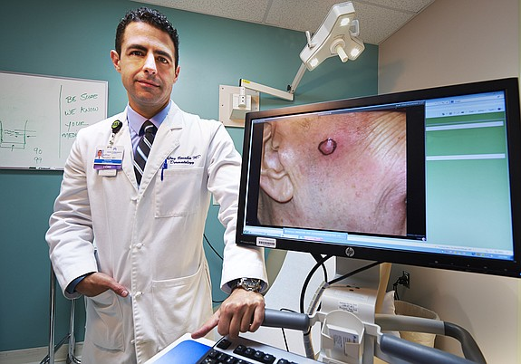 Jeffrey Benabio, dermatologist and physician director of health care at Kaiser Permanente in San Diego, examines photographs of skin anomalies, such as moles and rashes. Using high-resolution images, he can make recommendations for treatment.