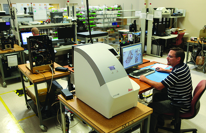 David Rybka, production manager at Leica Biosystems' Aperio ePathology division, confirms the scan quality of an Aperio AT2 image capture device at its production plant in Vista.