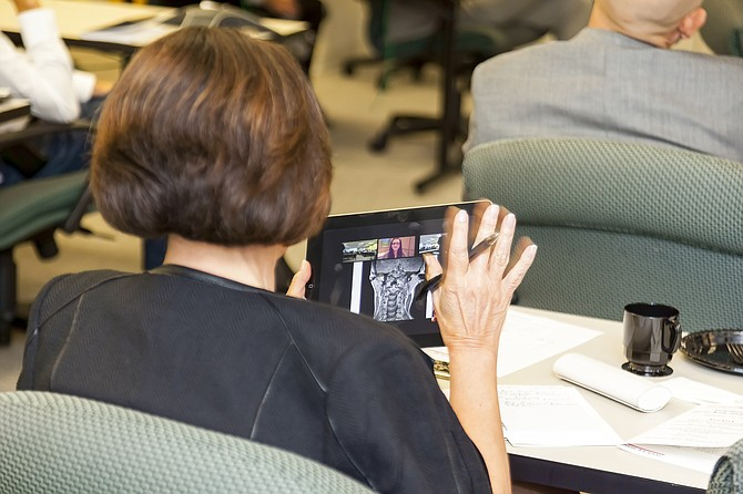 An audience member views telemedicine by tablet computer during a recent panel discussion on the topic.