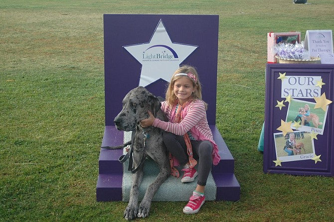 Beau Beau, a therapy dog, and an unidentified child participated in the recent LightBridge Walk that raised money for programs supporting people in hospice care.