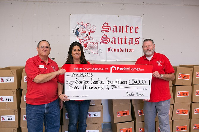 Santee Santas Foundation board members, from left, Sam Modica, Gail Ramer and John Morley accept a $5,000 check from Pardee Homes and the Weyerhaeuser Company Foundation.