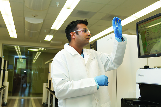 Suneer Jain, a lab manager at Illumina Inc., looks at a slide at the company's facility.