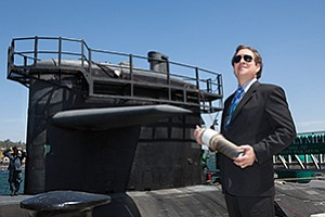 Dave Phillips, an electrical engineer at Space and Naval Warfare Center Pacific, stands in front of the submarine USS Olympia at Naval Base Point Loma. His work improves the ability to communicate with such submarines at sea.