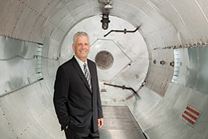 Frank Belknap, CEO of Vanguard Space Technologies Inc., stands in the company's 12-foot diameter autoclave. The $1.4 million pressure vessel is used to heat and cure satellite components, making them ready for space.