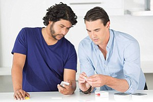 Ayub Khattak, left, and Clint Sever of Cue demonstrate their company's self-diagnostic device, also called Cue, which interfaces with a smartphone app, shown at right.