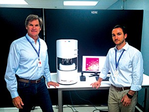 Paul Larson, left, and Matthew Barre of Daylight Solutions stand by their Quantum Cascade Laser microscope. Previous instruments of its kind were much larger in size.