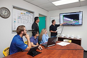 Mark Schull, Marco Ruelas, Jake Jaenicke, Neal Delos Santos and Wendy Anderson review a project's 3-D building information modeling for Balfour Beatty Construction.