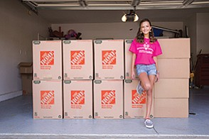 Eleven-year-old Trinity Barbera stands with the boxes of 2,000 shoes she collected during her summer break to help Soles4Souls reach its goal of 25,000 shoes for needy children.