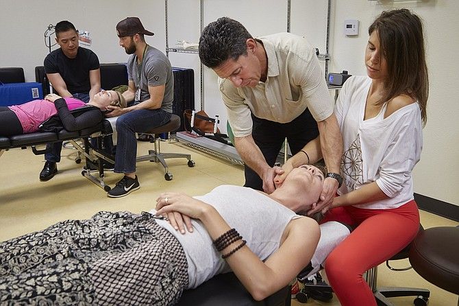 Dr. Joseph DeArmas instructs Bastyr University student Elly Lieppman on how to manipulate the spine of another student, Morgan Petersen.