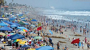 Beaches, such as this one in Oceanside, are a natural draw for summer tourists though overcast skies dampened numbers over the Fourth of July weekend.