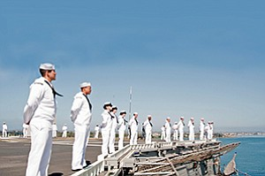 Sailors man the rails on the flight deck of the amphibious assault ship USS Peleliu (LHA 5) as it transits San Diego Bay.
