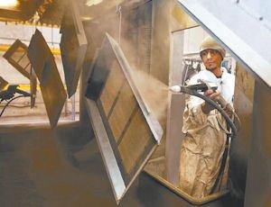 Finishing: A Powder Coating Plus employee applies a finish to sheet metal.