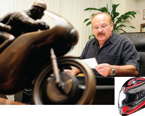 Motorcycle: Helmet House co-founder, Bob Miller, looks over paperwork in his office. The motorcycle sculpture was commissioned by the two partners.